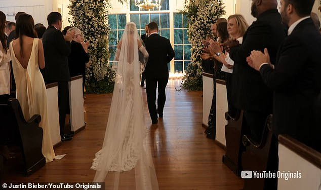 Their special day: Another glimpse of their wedding in South Carolina as they walk down the isle for the first time as husband and wife