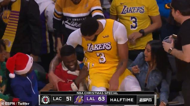 Lap sit: Lakers power forward Anthony tumbled into Kevin's lap right before halftime and the 6ft 10in player wrapped his arm around the 5ft 4in actor