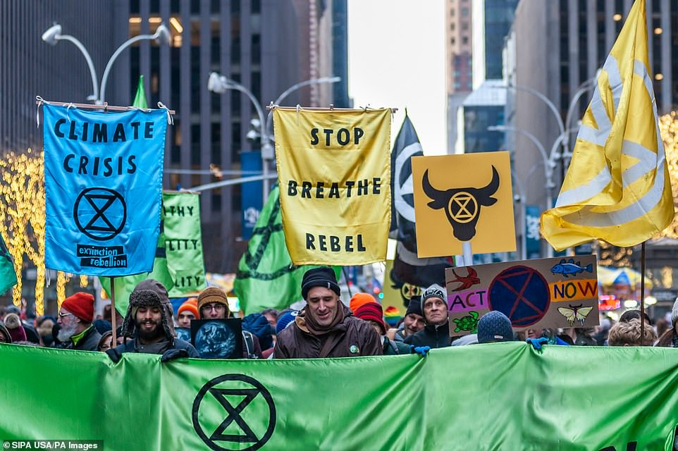 Protesters from the Extinction Rebellion group walk in a procession to Rockefeller Plaza in New York City on December 21