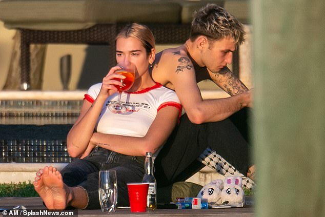 Picture perfect: The young lovers relaxed for a moment as the sun went down, Lipa taking a sip of her drink while leaning against Hadid