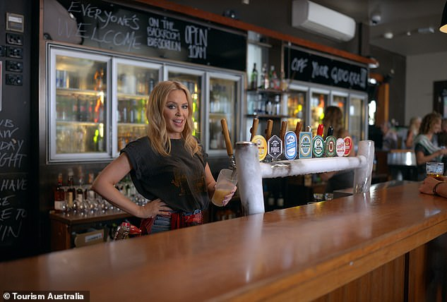 Pulling pints: Kylie pictured in an 80s-inspired ensemble pulling pints in a pub during the promotional video