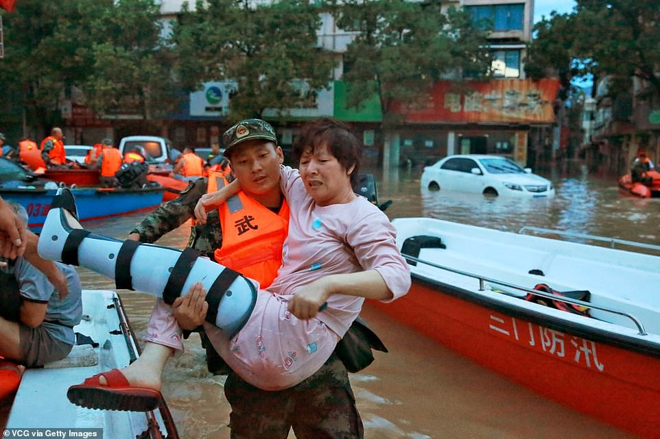 A rescuer carries an injured woman across a flooded street in China after Typhoon Lekima hit the country in August 2019