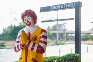 Ronald McDonald figure in front of drive through sign