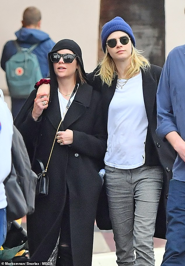 Casual: Cara donned a stylish blue beanie hat during the day which she paired with some chic checked trousers