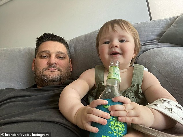 Daddy's girl! Tobi, who celebrated her first birthday back in November, showed off her cheeky grin as she clasped onto the glass bottle in its stubby holder as her radio host father starred blankly