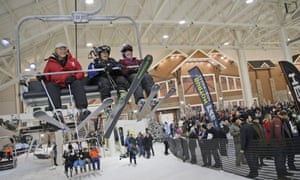 Skiers ride one of the first chairs up the hill during the grand opening of Big Snow in the American Dream mega-mall.