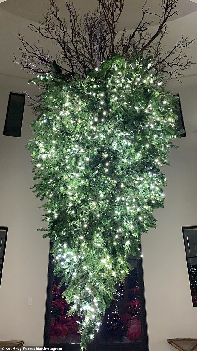 Surreal: In Kourtney's foyer, there was a large Christmas tree decorated with white lights hung upside down with roots reaching to the high ceiling