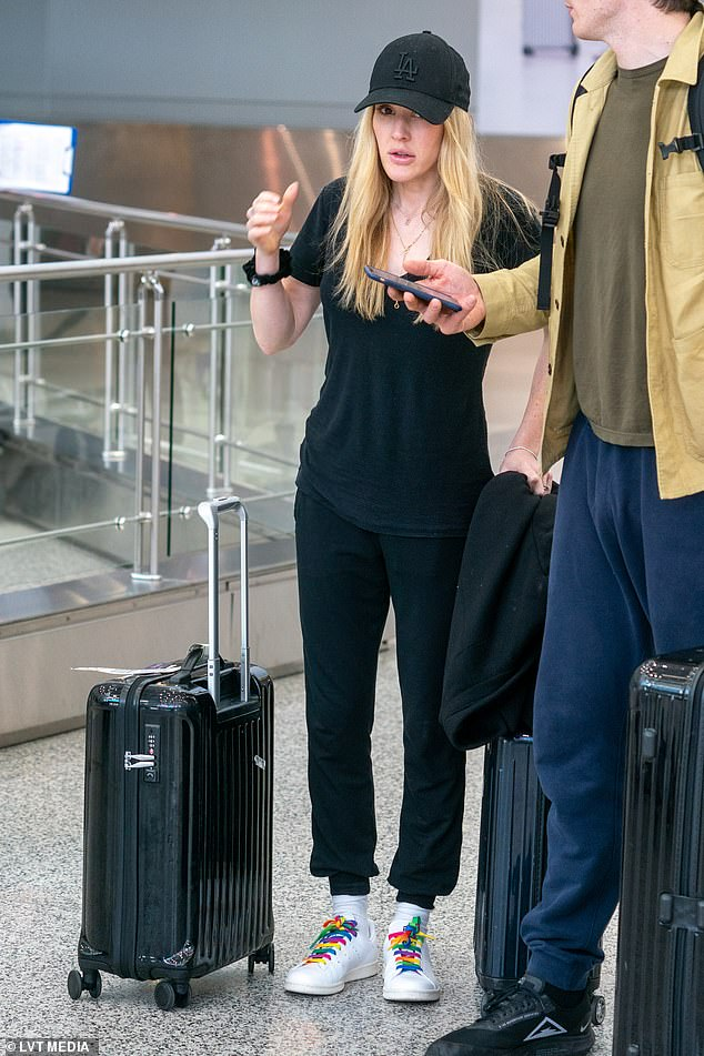 Low-key: The British singer - who turns 33 on Monday - opted go makeup free for her lengthy flight as she wheeled her luggage through the Florida terminal