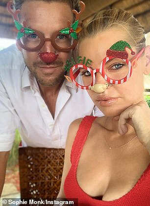 Festive mood: Later, Joshua wore Rudolph-inspired glasses, while Sophie opted for a candy cane print variety