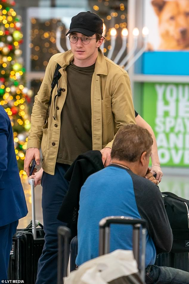 Low-key: Her artist husband Caspar also opted for a low-key ensemble as he arrived in Florida with his wife