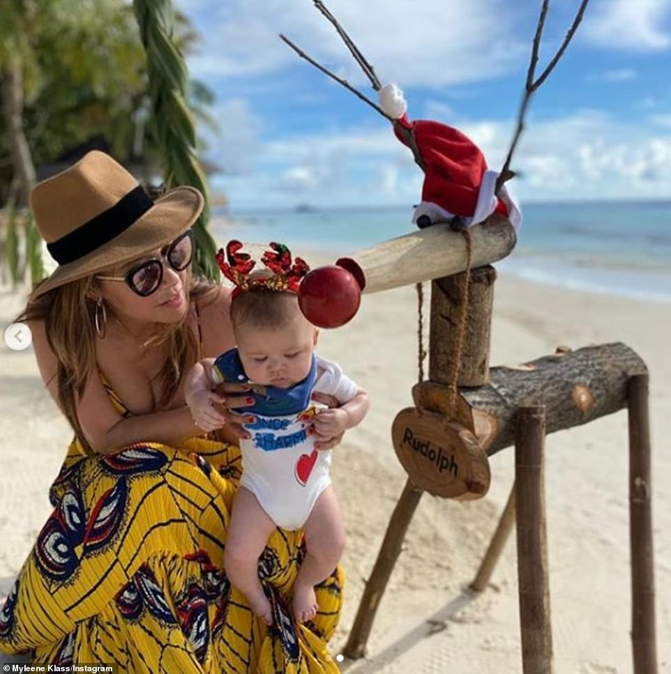 Sweet: The radio presenter, 41, took to social media to post a sweet photo with her baby son Apollo, four-months,as they posed next to a wooden Rudolph the Red-Nosed Reindeer statue on the beach