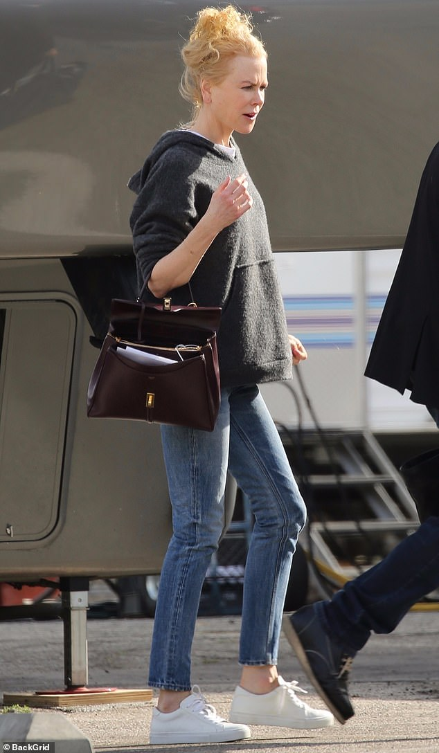 Keeping it cozy: The 52-year-old donned an oversized grey knit hoodie, paired with slim faded jeans and white sneakers