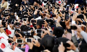 Spectators use smartphones, trying to capture images of the royal motorcade in Tokyo