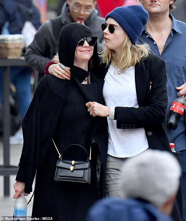 Messing around: Cara wrapped her arms around Ashley, causing her to smile as they walked
