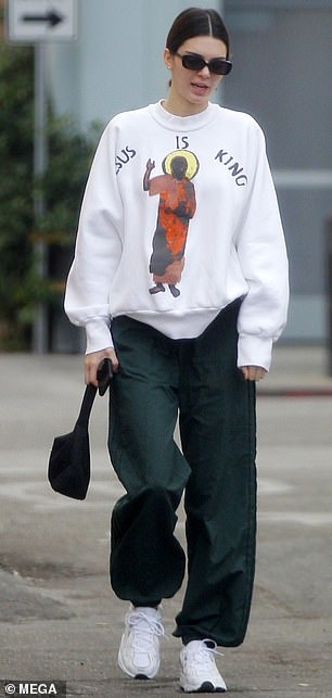 Cool kicks: Kendall paired the loose-fitting top with emerald green track pants and a pair of white sneakers