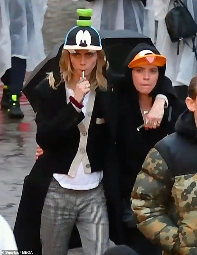Happy: During the day Cara buttoned up her black jumper which had a cream trip to try and keep warm