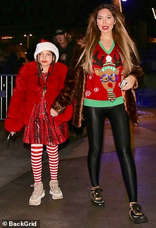 Bundled up: Sophia bundled up in a Santa cap and thick red coat over a plaid dress along with candy cane leggings.