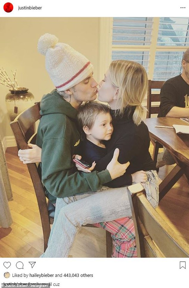 Lots of love: The Canadian crooner's young cousin was seated on his lap as he and his wife smooched