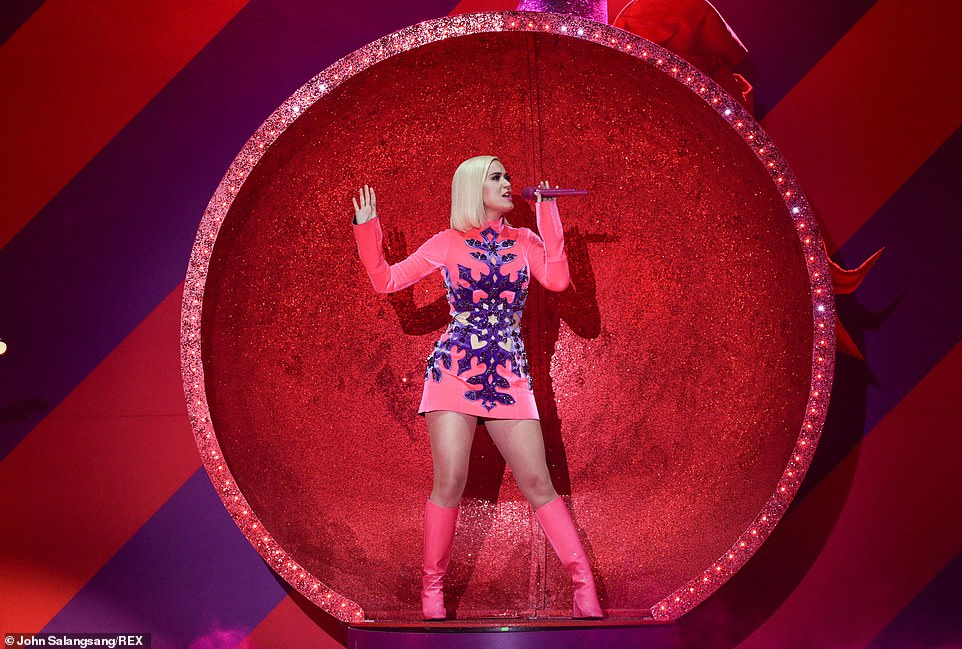 Think pink: The American Idol host made the most of her incredible figure in a hot pink minidress which featured glittering purple detailing