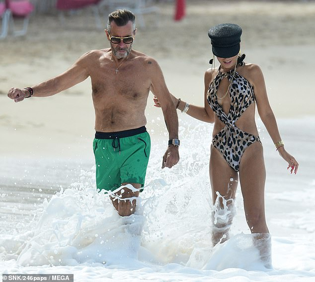 Loving it: Despite the hot weather, Duncan and his stunning wife Nigora enjoyed a relaxing stroll through the ocean