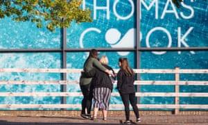 People comfort each other outside the Peterborough headquarters of Thomas Cook.