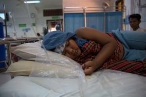 Chan Piseth lies in bed at Angkor hospital