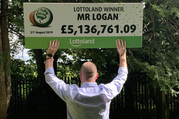 Mr Logan stands proudly with his £5.1 million winnings from Lottoland