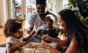 Multi-ethnic family enjoying opening presents together in their pyjamas on Christmas morning