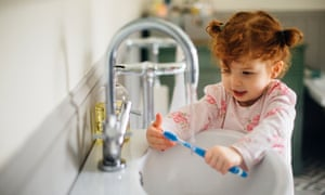 Little girl in the bathroom of her home in her pyjamas. She is rinsing off her toothbrush after brushing her teeth.