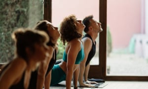 Scene Of A Group Of People Practicing Yoga In Class.