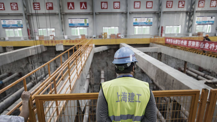 A worker stands overlooking an open pit at a construction site for Line 14 of the Shanghai Metro system in Shanghai, China, on Tuesday, July 11, 2017. The world's second-largest economy is forecast to slow from the first quarter, when it posted the first back-to-back quarterly acceleration in seven years, though it is still on track to remain above the leadership's growth target of at least 6.5 percent. Photographer: Qilai Shen/Bloomberg
