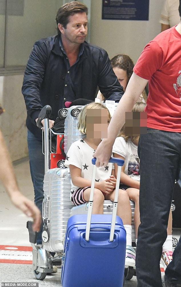 Back to reality: Steve appeared downcast as he pushed along a baggage trolley, on which his two daughters,Isabella, eight, and Francesca, six, were sitting