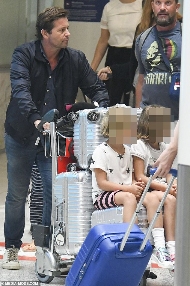 Daddy cool:Steve dressed casually for the flight in a blue shirt, a matching jacket and jeans