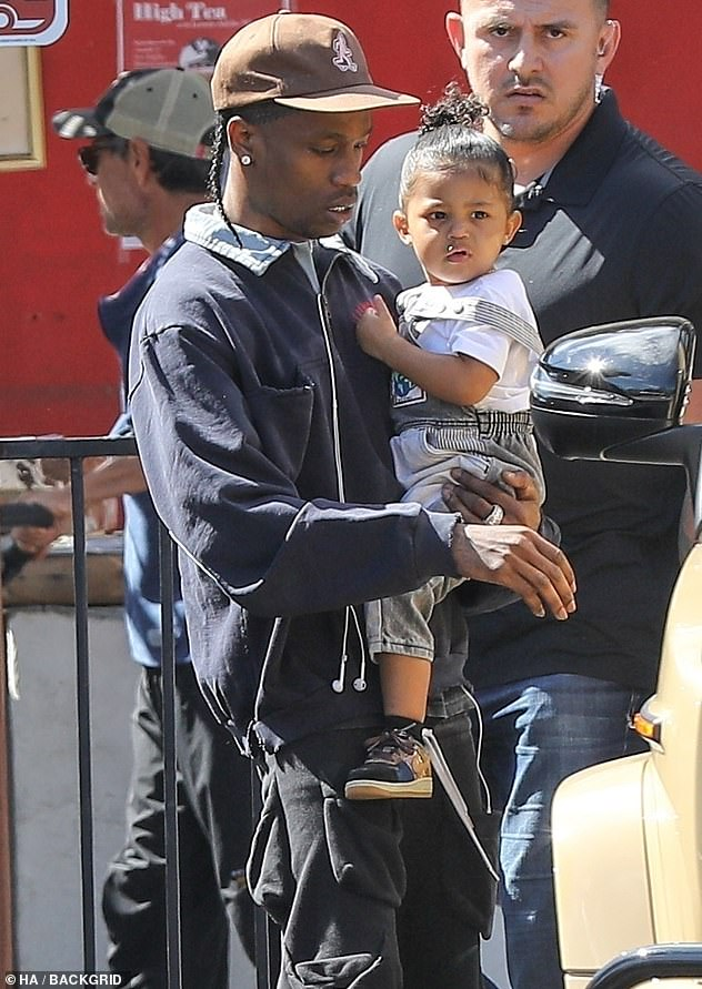Cool dad: Travis, 27, rocked a blue zip-up jacket with a brown baseball cap and black cargo pants