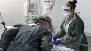 Nurses caring for a patient in ICU