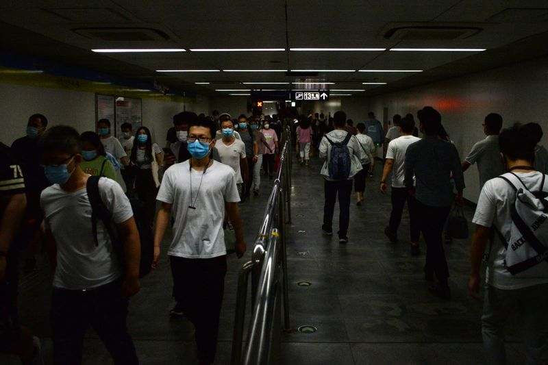 © Reuters. People wearing face masks walk inside a subway station, following the an outbreak of the novel coronavirus disease (COVID-19), in Beijing