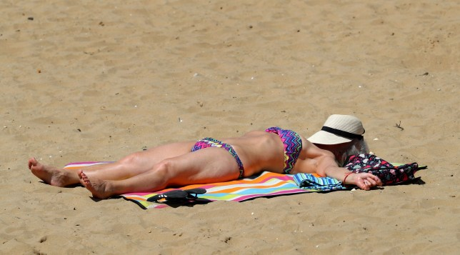 A lady relaxes in the sunshine on the beach in Margate, Kent