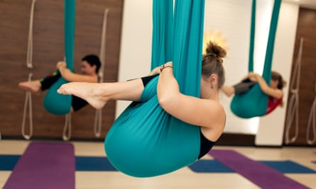 A group of women are hanging in a foetal position in a hammock during an aerial yoga class.