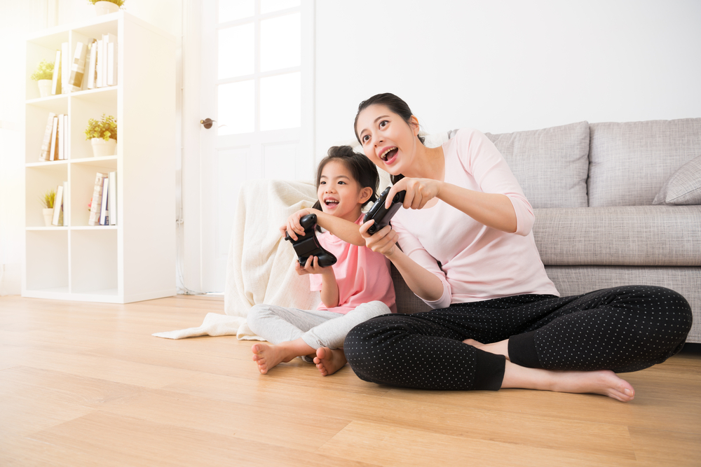 Shutterstock_634787303 good relationship cute little girl with young mother using joystick playing video game sitting together in living room wooden floor enjoying family holiday.