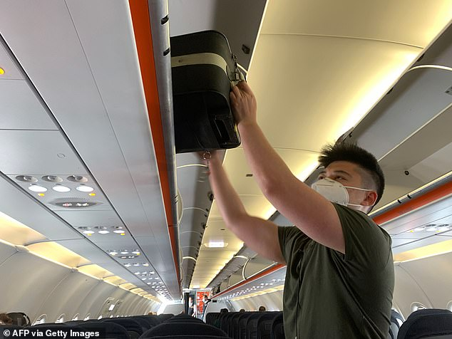 All UK arrivals – including Britons – must now fill in an online 'contact locator' form setting out where they will live for a fortnight. Refusal to do so risks a £1,000 fine. Pictured: An EasyJet passenger boards a flight while wearing a face mask