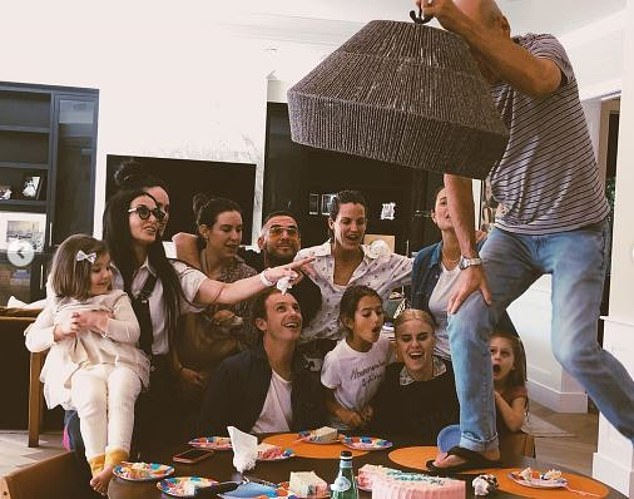 Wild times:The trio of family photos also showed action star Bruce climbing on the kitchen table