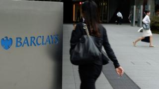 People walking by a Barclays sign