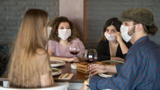 People in masks dining out