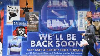 """Man walking past theatre poster saying """"We'll be back soon"""" outside the Sondheim Theatre in London"""