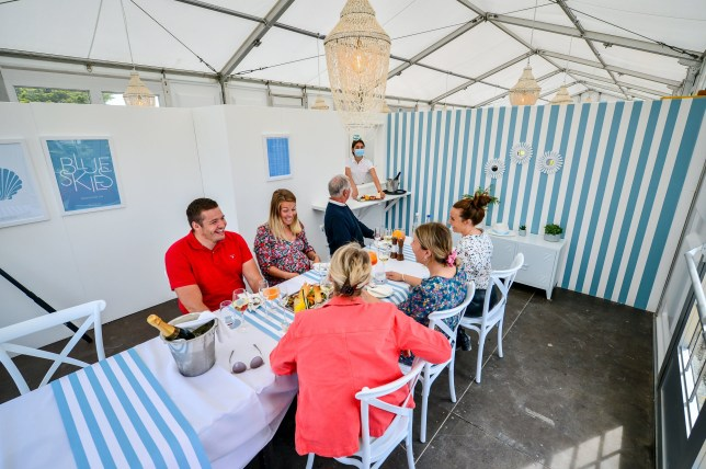 Diners take their places in family bubbles to test the UK's only purpose built pop-up socially distanced restaurant, split into separate dining pods with serving hatches under one marquee, the Anti Social Club, in Polzeath, Cornwall, where staff are training for dinner service in preparation ahead of reopening to guests when lifting of further lockdown restrictions in England comes into effect on Saturday.