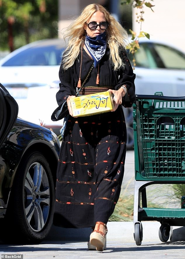 Chic: The 51-year-old fashion designer looked typically cool in a patterned black maxi dress, which she accessorized with a pair of over-sized black sunglasses and wedge espadrilles sandals; here she is seen with LaCroix