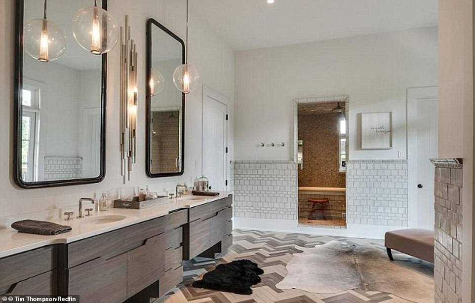 Elegant: A bathroom is composed of large mirrors with wooden cabinets and globe lamps