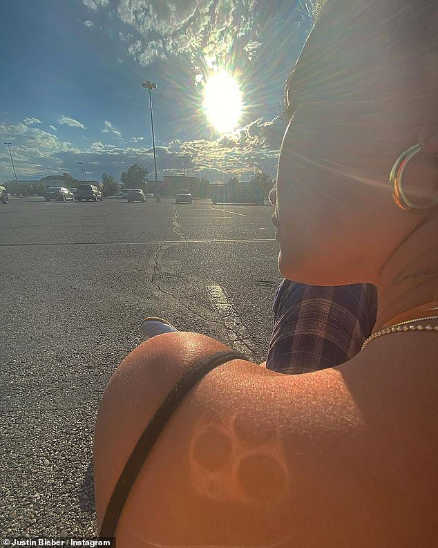 Natural beauty: Justin captured a gorgeous shot of Hailey sitting in a parking lot as the sun began to set