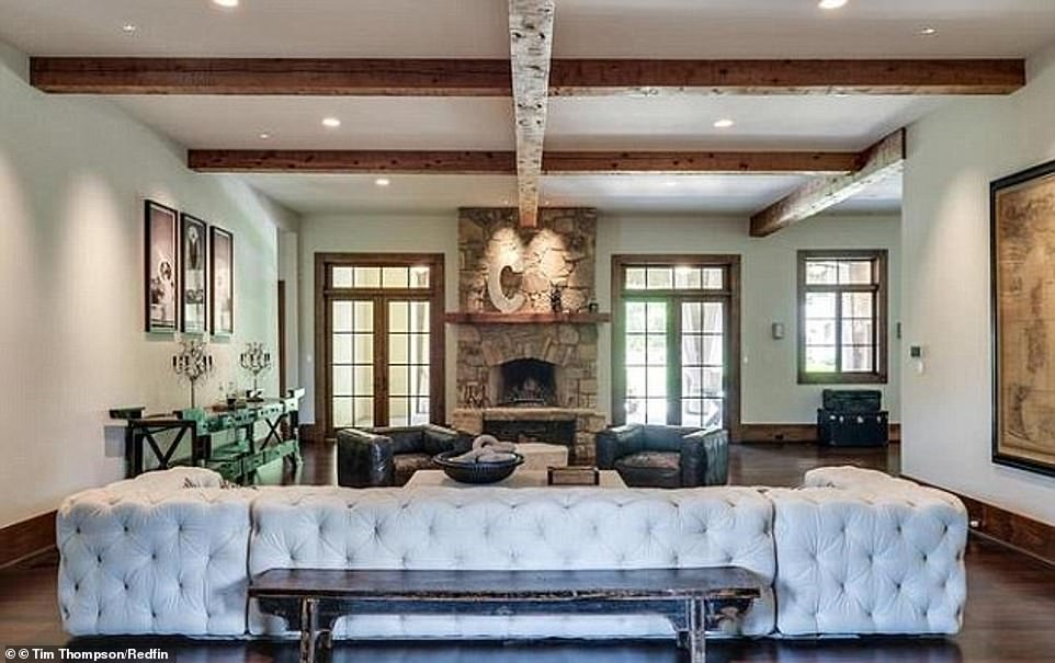 Amazing: A large living room area has a massive fireplace and wood-beamed ceiling.