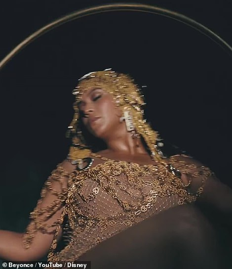 Bey gold:The icon is also seen decked out in all gold, with a shimmering gold dress and a gold headdress as well, as she's seen swinging on a golden hoop swing
